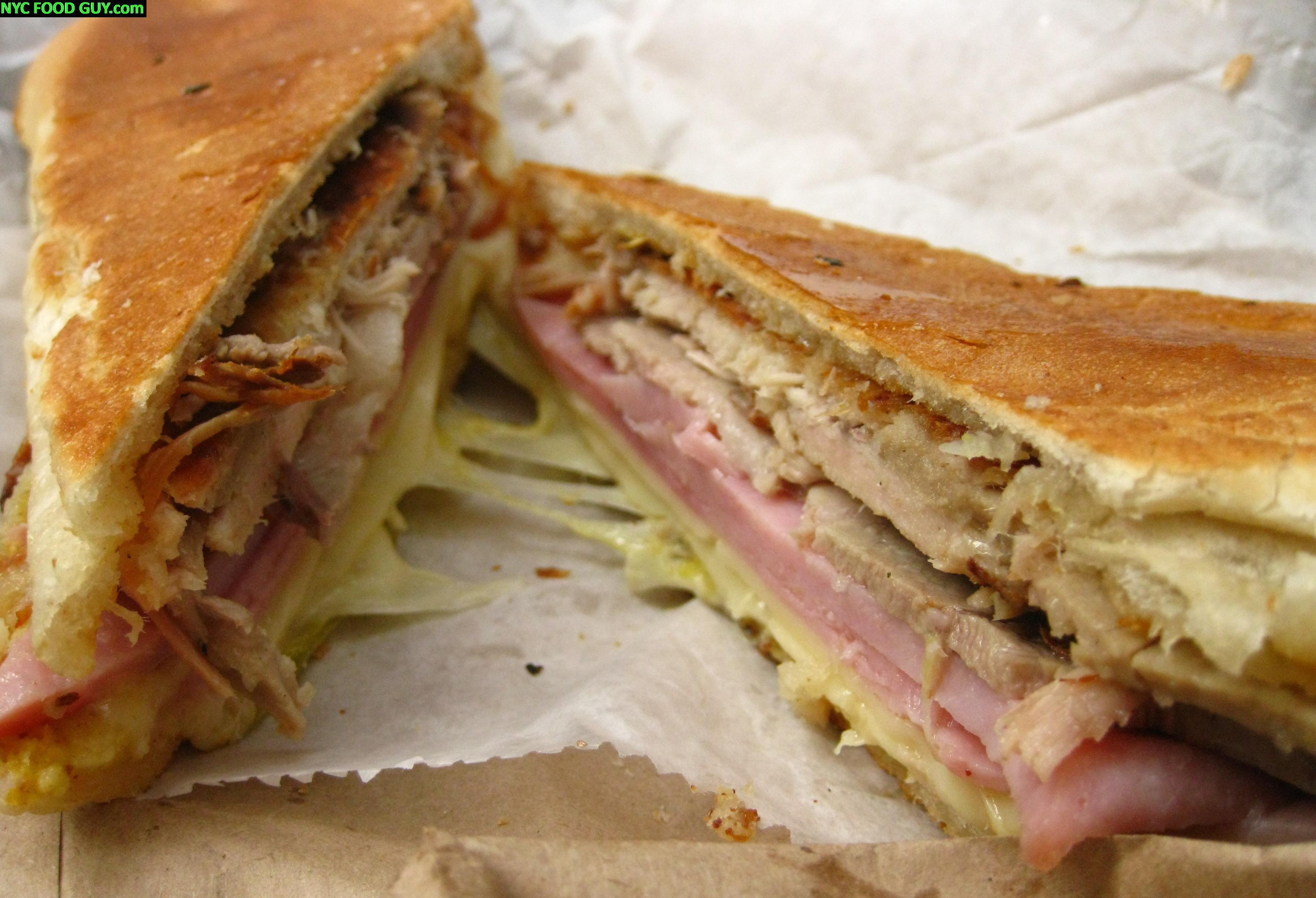 El Sitio Cuban Sandwich ($4.35). From Top to Bottom: Pressed Garlic-Butterd hero, roast pork, sliced ham, melted Swiss, pickles, mustard